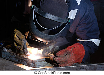 TIG welding of metal frame close up - TIG welder uses torch...