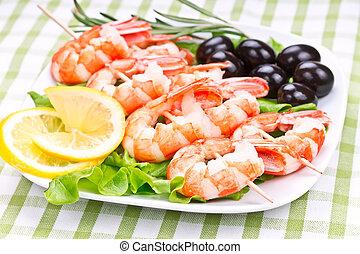 tiger prawns on a skewer with olives and lemon