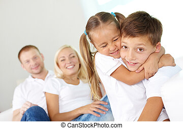 Portrait of happy children in embrace with their parents behind