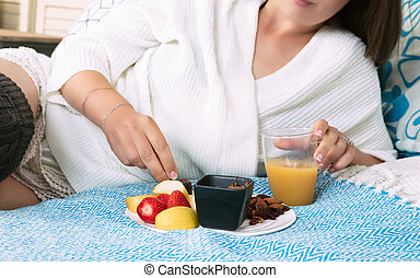 Tight shot of a young woman having breakfast in her room