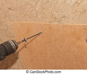tightening the screws into the wood wall