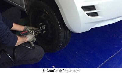 Tightening the screws of a car tire with a pneumatic...