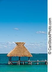 Tiki Hut on dock with blue ocean and sky