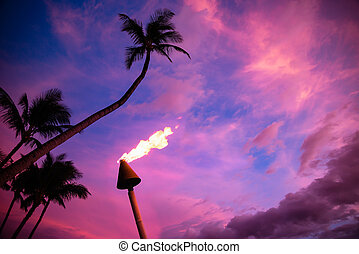 Tiki torch against colorful tropical sunset with palm trees