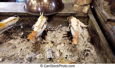 Tilapia Is Cooked On a Rotating Spit Over Coals At A Market.