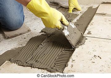 Tile flooring installation - Man making the ceramic tile ...