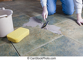 A man repairing the grout on a tile floor
