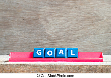 Tile letter on red rack in word goal on wood background
