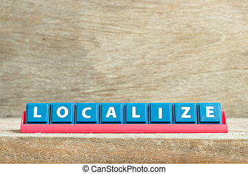 Tile letter on red rack in word localize on wood background