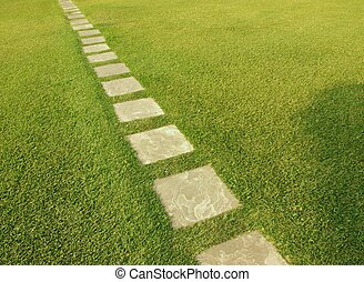 Tile path streching on green grass - Direction of old rustic...