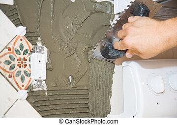 Tile Setter Scores Mortar - Closeup view of a tile setter...