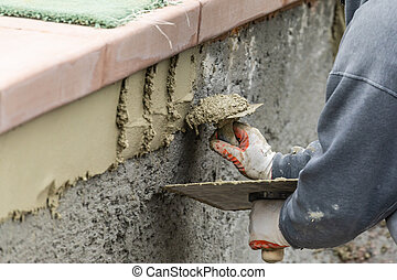 Tile Worker Applying Cement with Trowel at Pool Construction Site.