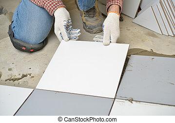 Worker installs ceramic tiles on a floor