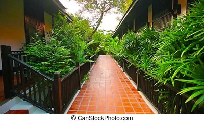 Video Full HD - Strolling along a beautiful, tiled, outdoor walkway between the cottages at a luxury resort near Sukhothai, Thailand.