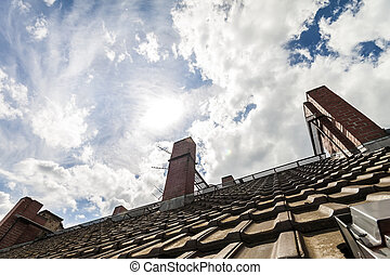 Tiled roof with dark orange bricks and yellow chimneys against dramatic blue sky with white clouds