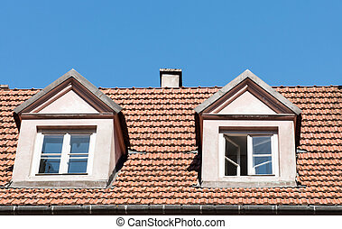tiled roof with windows against the blue sky