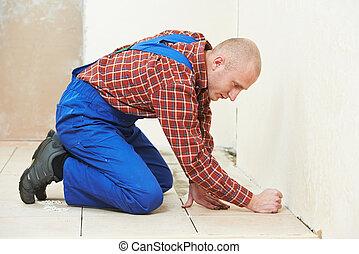 professional tiler builder worker installing home floor tile at repair renovation work