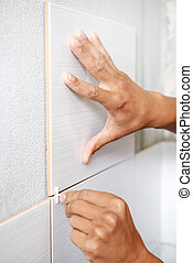 Close-up view of tiler hands fixing wall tile with spacers at home repair renovation work