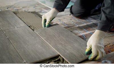 tiler is installing ceramic floor tiles above cement and...
