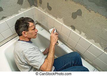 Tiling the Bathroom - Man working in a tight space while...