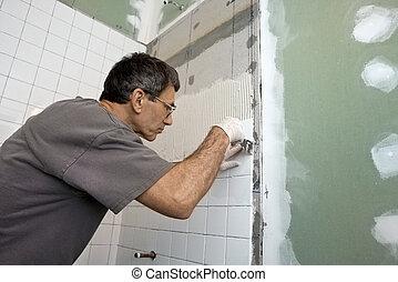 Tiling the Bathroom Tub Enclosure - Man applying ceramic...