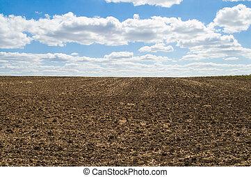 tillage - arable soil at autumn under blue sky