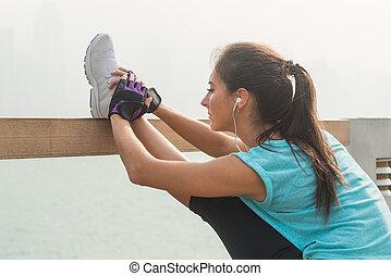 tillsluta, skott, av, ung, fitness, kvinna ute arbeta, på, staden, gata, gör, träningen, sträckande, henne, ben, stående, in, en lodlinje, splittring, och, avlyssna musik, in, headphones.