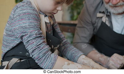 Tilt-down of old man and serious child in aprons making pot from clay working on throwing wheel concentrated on creative traditional activity.