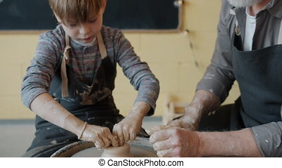 Tilt-down of skillful kid in dirty apron working with clay on pottery wheel under supervision of adult potter. Leisure activities and craftsmanship concept.