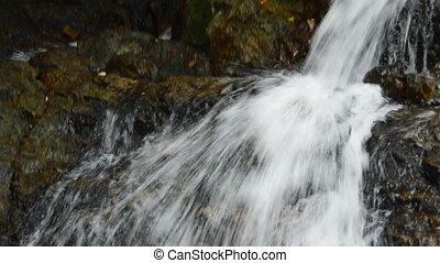 tilt down of waterfall falling and hit rock splashing to...