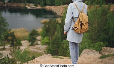 Tilt-down slowmotion portrait of slender girl walking on the...