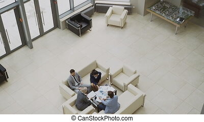 Tilt down top view of group of business people colleagues discussing financial charts sitting on couchs in lobby at modern business center