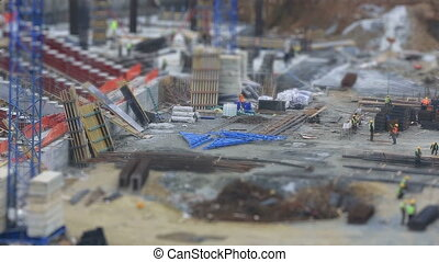 tilt shift effect time lapse construction zone with heavy equipment and workers (miniature effect)