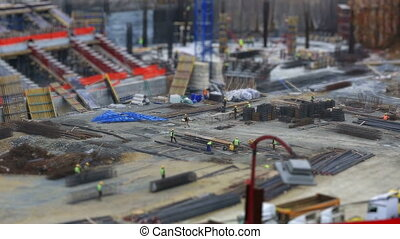 tilt shift effect time lapse construction zone with heavy equipment and workers (miniature effect), dolly shot