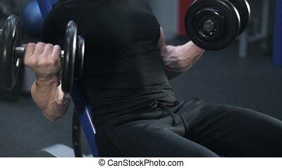 Tilt up of a man in black doing a dumbbell exercise in gym
