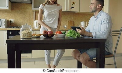 Tilt up of Attractive couple chatting in the kitchen early morning. Handsome man using tablet while his girlfriend cooking