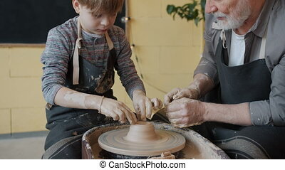 Tilt-up of boy in apron shaping clay on throwing wheel while old man is speaking teaching young apprentice. Arts class and communication concept.