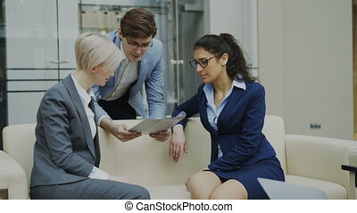 Tilt up of Cheerful businessman talking and discussing about financial report with business female colleagues sitting on sofa in meeting room
