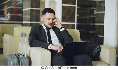 Tilt up of confident businessman talking mobile phone and using laptop computer while sits on armchair in luxury hotel with luggage near him. Travel, business and people concept