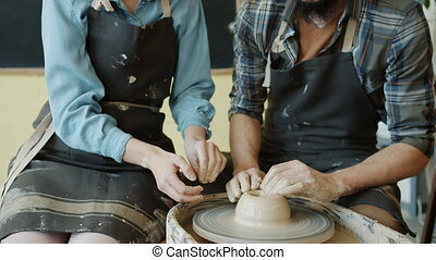 Tilt-up of girl and guy shaping clay on pottery wheel ...