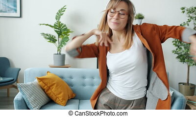 Tilt-up of happy female student wearing headphones dancing and singing indoors in house. Leisure time activities and human emotions concept.