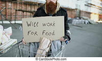 Tilt up of portrait of young homeless man with cardboard looking at camera and wants to work for food standing near shopping cart