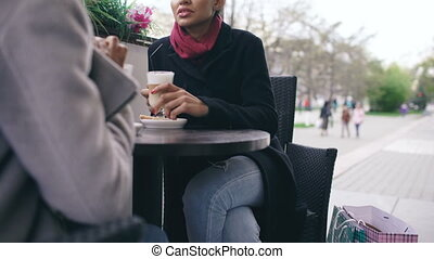 Tilt up of Two attractive mixed race women talking and drinking coffee in street cafe. Friends have fun after visiting mall sale