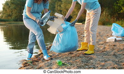 Tilt-up of two female eco activists picking trash on the beach working together