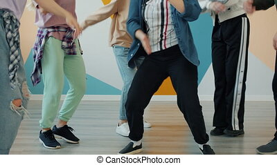 Tilt-up portrait of teenage dancers having fun in creative studio together learning modern moves dancing indoors. Youth culture and hobby concept.