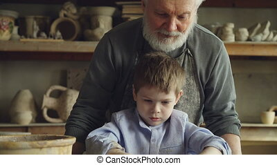 Tilt-up shot of concentrated little boy making clay figure...