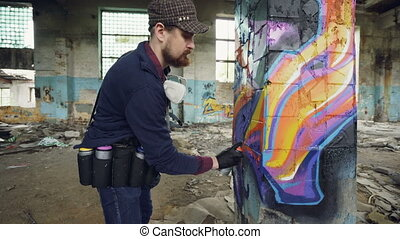 Tilt-up shot of creative bearded guy painting graffiti on...