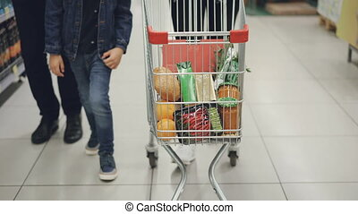 Tilt-up shot of happy young family pushing shopping trolley...