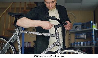 Tilt-up shot of young man bike repairman fixing broken...