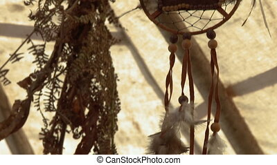 Tilt up to a dreamcatcher hanging in a tent - Close up of a...